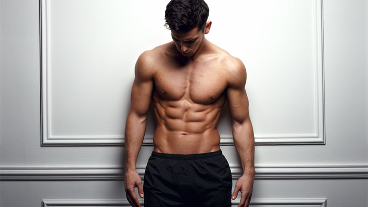 Athlete, muscular man at the white wall poses shirtless, showing six pack abs, white background