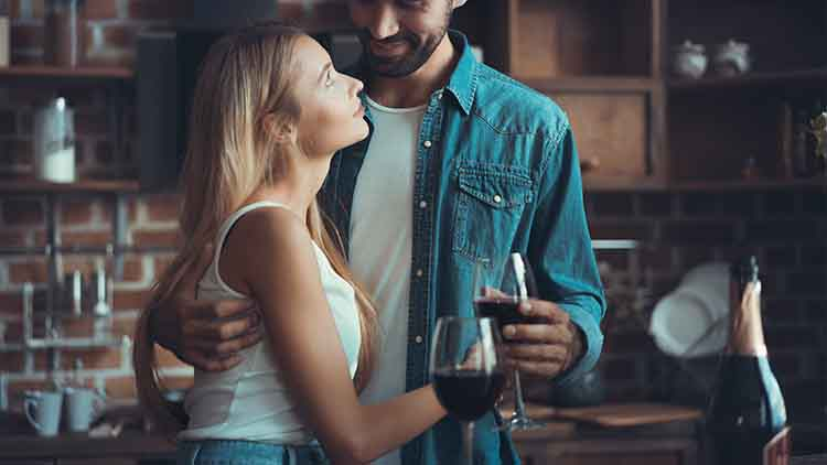Beautiful young couple is drinking wine and smiling while cooking in kitchen at home.