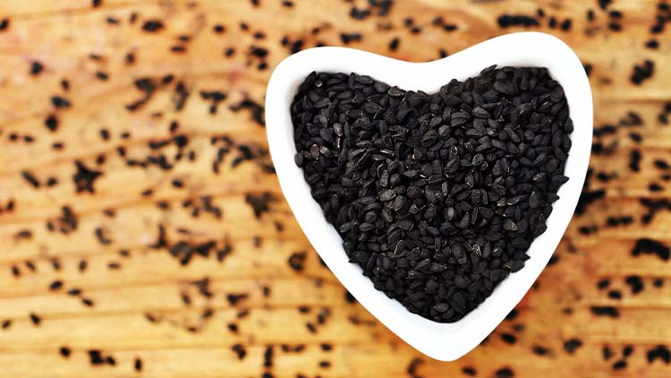Black cumin (nigella sativa or kalonji) seeds in heart-shaped bowl on wooden background