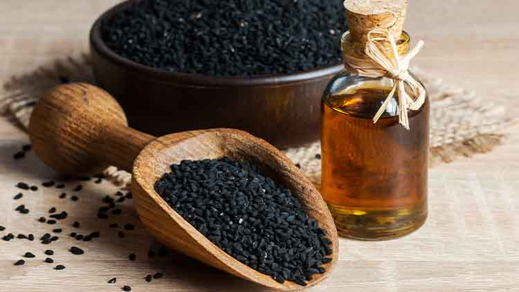 Black cumin seeds and essential oil with bowl and wooden shovel or spoon. Nigella Sativa in glass bottle. Organic herbal medicine for many diseases