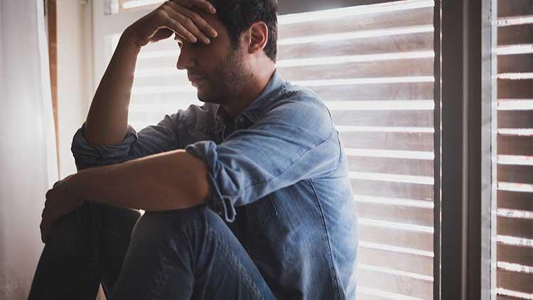Depressed man sitting next to the window
