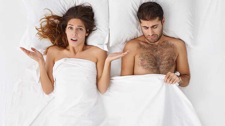 Displeased indignant Caucasian woman shrugging shoulders with open palms after her husband couldn't perform sexually again. Frustrated male having erectile dysfunction, lying in bed with his wife