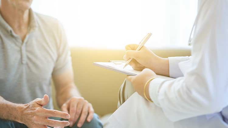 Faceless view of senior man talking to doctor in bright light while taking notes on clipboard