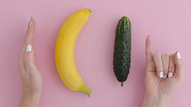 Girl jokingly measures the size of a banana and cucumber