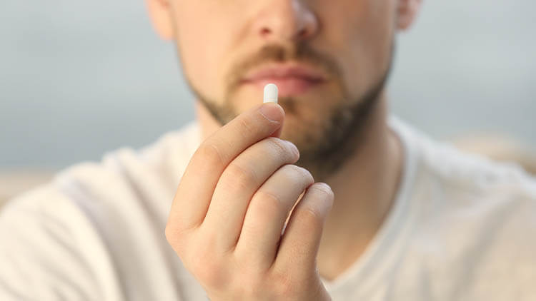Hand of young man with pill, closeup