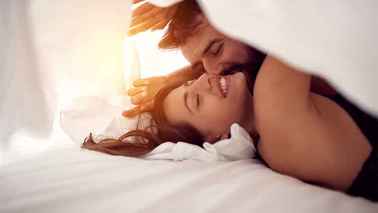 Happy couple having fun in bed.