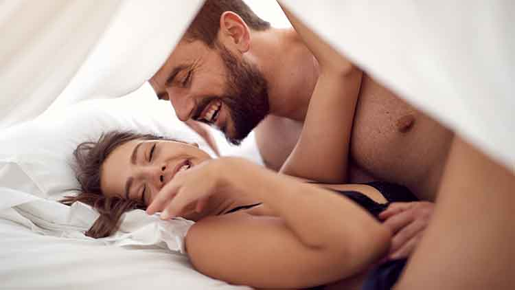 Happy lovers making love in bedroom.