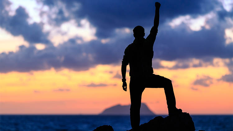 happy and strong man standing on a rock with his arm held above his head looking at the sunset