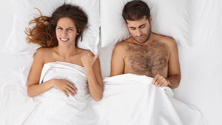 Indoor shot of unhappy frustrated bearded Caucasian man looking under white blanket at his penis, worried because of erectile dysfunction or small size, his wife pointing at him, having disgusted look