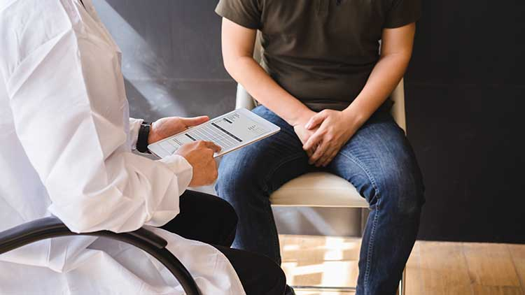 Male doctor and testicular cancer patient are discussing about testicular cancer test report.