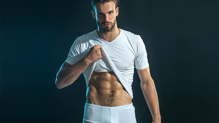 Man in boxer shorts shows his abdominal muscles, raising his t-shirt with his hand. Young athletic tanned man shows his muscles. Muscular sexy man in white t-shirt.