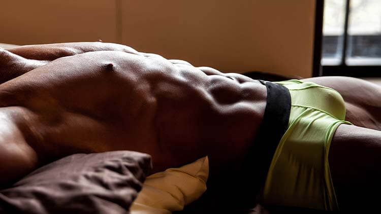 Muscular young sexy man lies on the bed