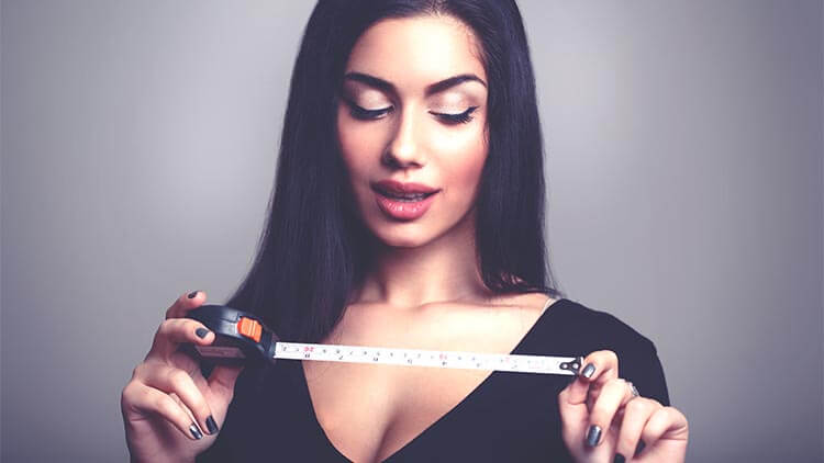 a woman holding a measuring tape looking excited