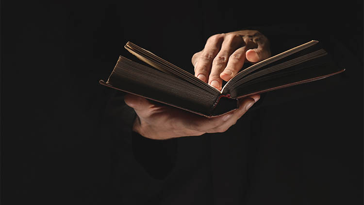 a priest holding an old bible in the dark on a black background