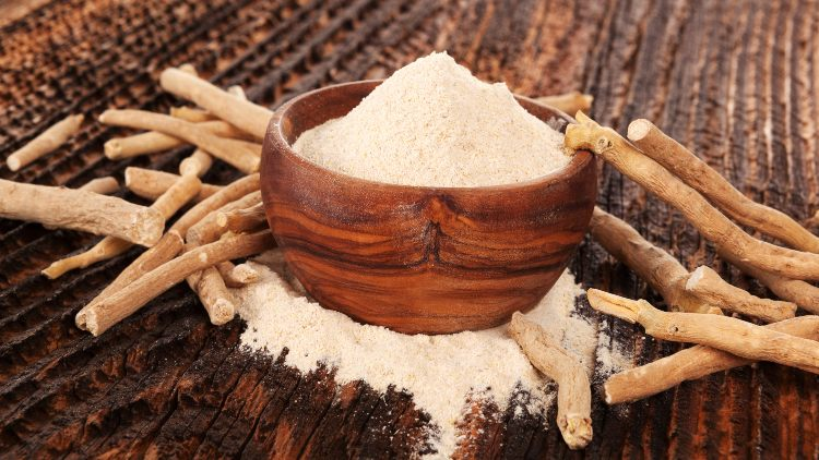 Ashwagandha powder in wooden bowl with stems on wooden table