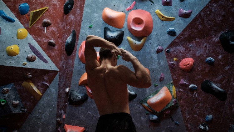 Athletic man stretching before bouldering