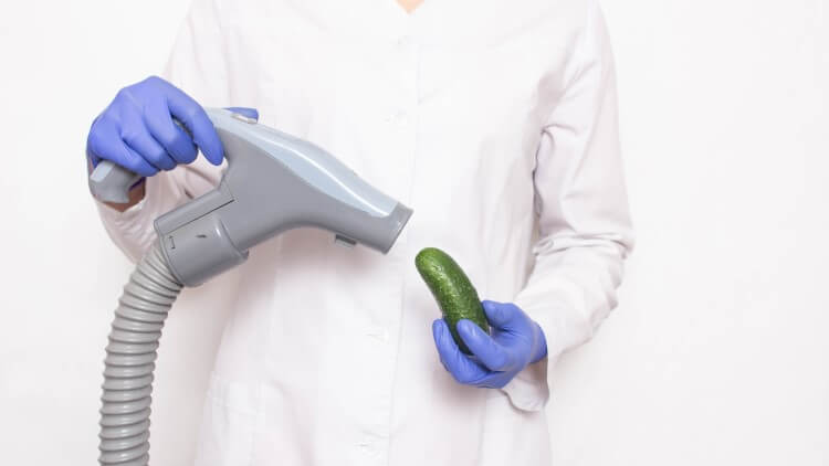 Doctor holding vacuum towards cucumber