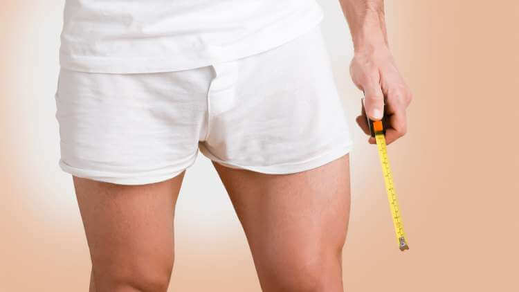 a man wearing only his boxers and a white t-shirt holding a measuring tool