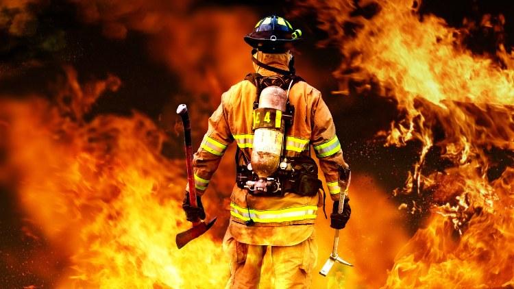 Firefighter staring into fire blaze