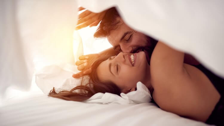 Happy couple having fun under sheets