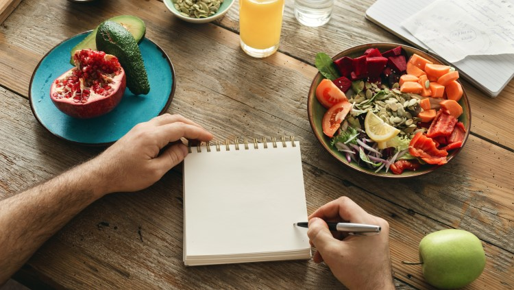 Healthy food on table with man writing notes