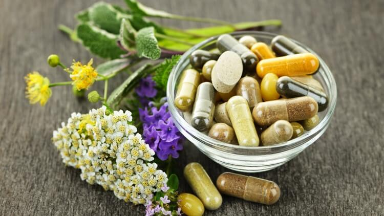 Herbal medicine and pills around bowl