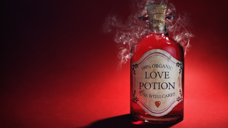 Bottle of love potion on red background