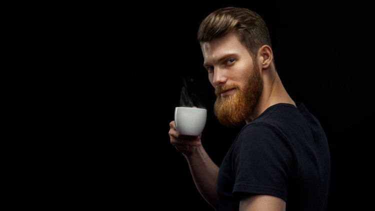 Man drinking hot coffee staring into camera