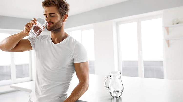 a man drinking from a bottle of water