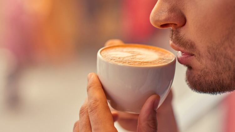 Man holding coffee close to lips