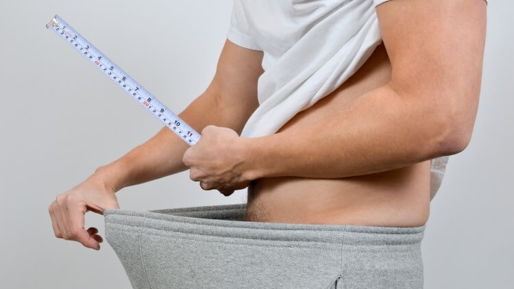 Man holding measuring tape above groin area
