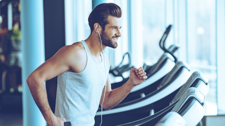 Man jogging on treadmill smiling with earphones in