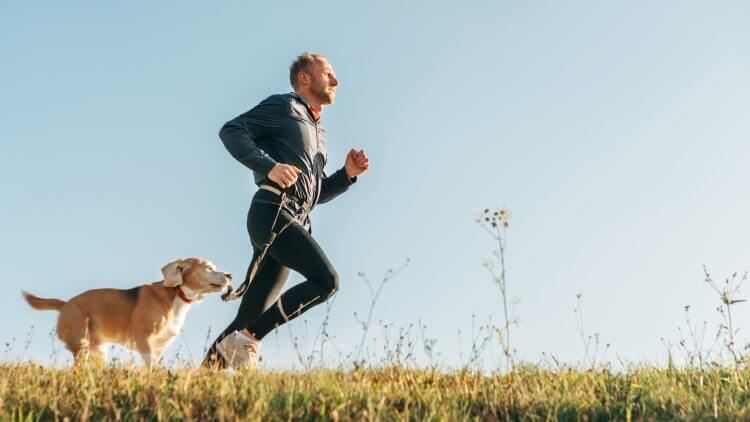 Man jogging through field with dog
