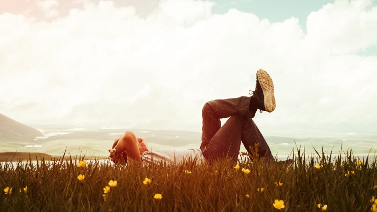 Man laying on grass staring into sky