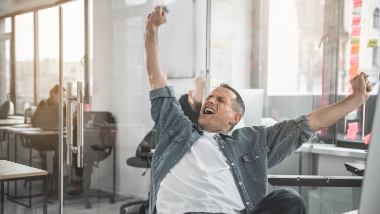 Man yawning and stretching at desk