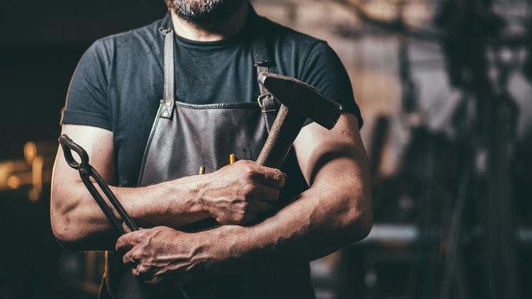 Muscular blacksmith wearing apron holding hammer