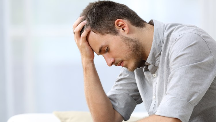 Sad man sitting on couch with hand on head