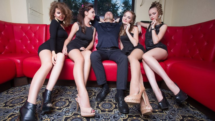 Smart man sat on red sofa with 4 women