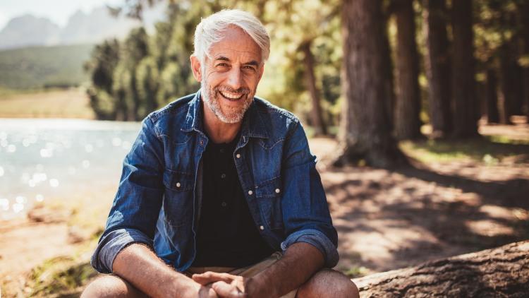 Smiling senior man sat on log by a lake