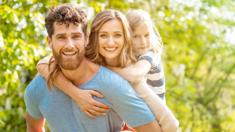 Strong man holding happy family on back