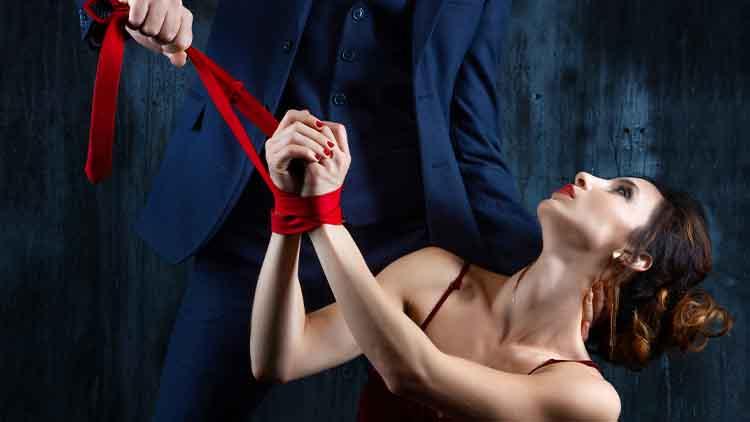 tied hands by red tie on dark background.