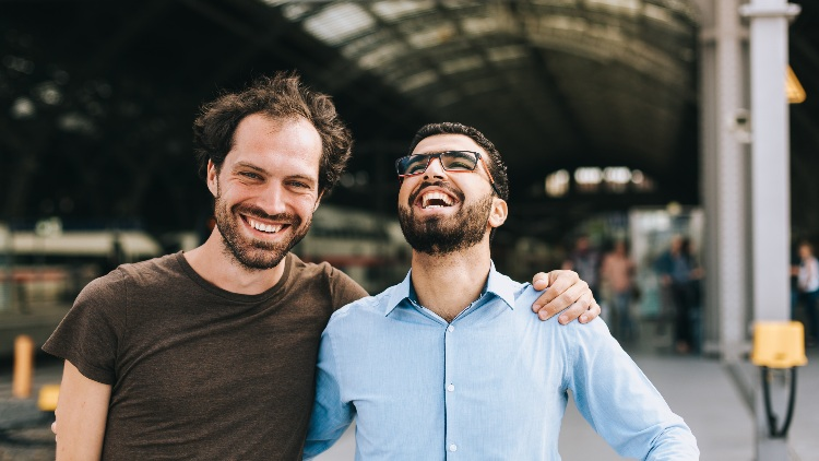 Two men laughing in train station with arm around eachother