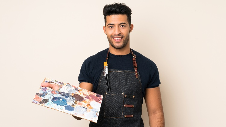 Young man holding paint palette smiling