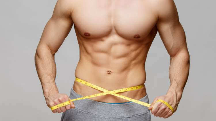 Young topless man with measuring tape around waist