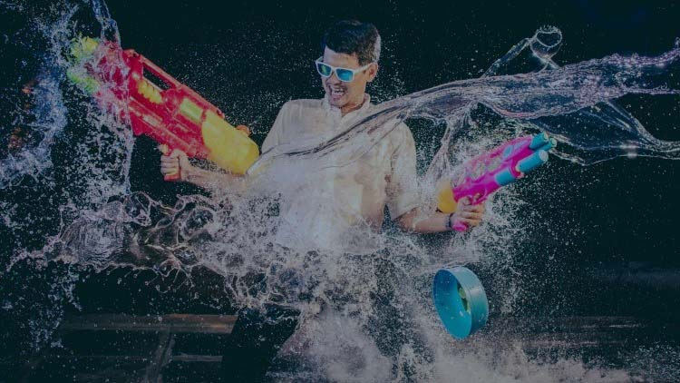 Young man using waterguns in water fight