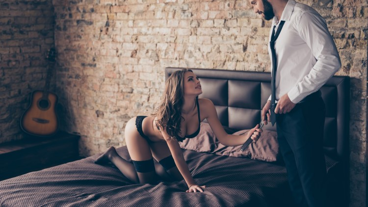 Young woman pulling partner into bed by his belt